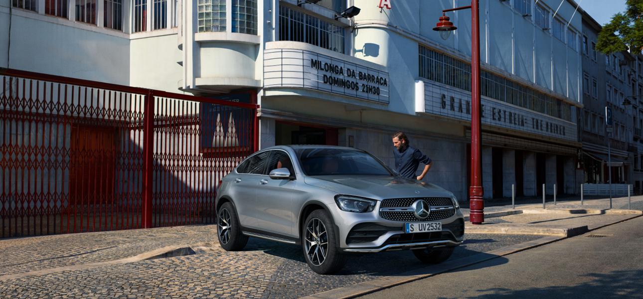 Mercedes GLC Coupé grise en arrêt - Vue de trois quarts du profil avec une personne à coté